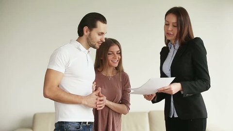 Young attractive happy smiling casual couple meeting consultant in office or at home. Cheerful husband and wife discussing contract and shaking hands with female contractor after reaching an agreement
