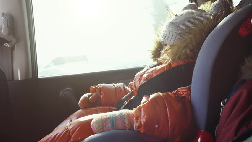 Dreaming cute child in a car in the child safety seat in slow motion on sunny day. 1920x080 | Shutterstock HD Video #25083746