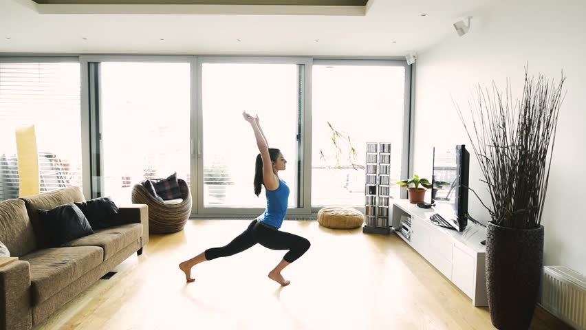 Young woman exercising at home, stretching legs and arms. | Shutterstock HD Video #25093535