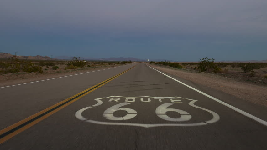 Dusk driving over Route 66 pavement sign in the Mojave desert in Southern California. | Shutterstock HD Video #25098995