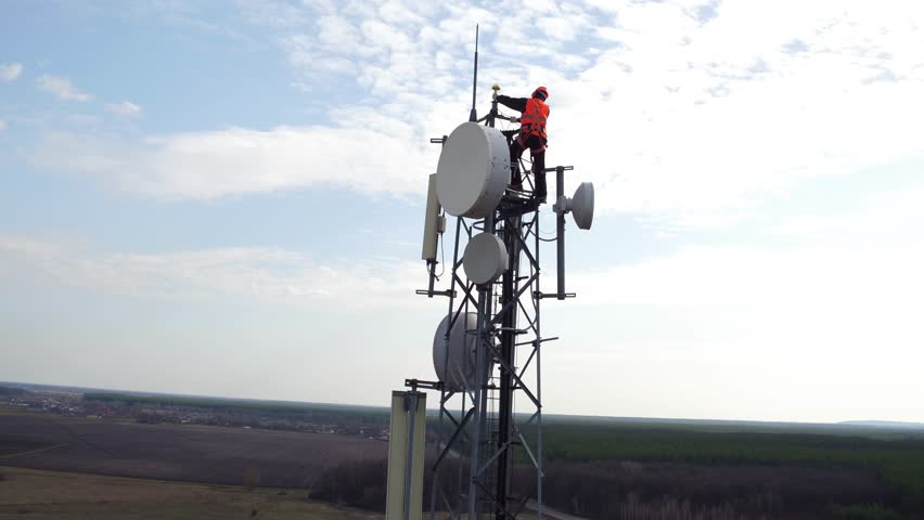 Worker servicing cellular antenna in front of sunlight, drone view of telecommunication antenna system, technician working on top of cellular antenna | Shutterstock HD Video #25122005