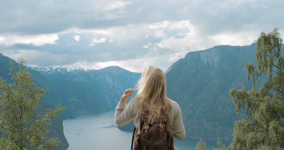 Woman taking panorama photograph fjords with smartphone photographing scenic landscape from high up nature background view enjoying Norway vacation travel adventure | Shutterstock HD Video #25126217