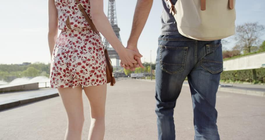 Young couple holding hands woman leading boyfriend walking towards Eiffel Tower Paris POV travel concept | Shutterstock HD Video #25127375