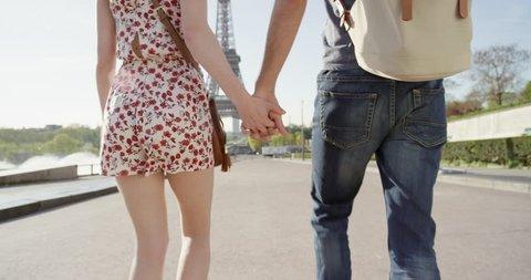 Young couple holding hands woman leading boyfriend walking towards Eiffel Tower Paris POV travel concept