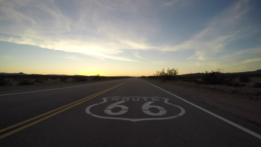 Route 66 pavement sign driving shot after sunset in the California Mojave Desert.