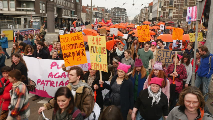 Amsterdam, March 11, 2017. Women's March walking through Amsterdam, protesters carrying orange signs and umbrella's.