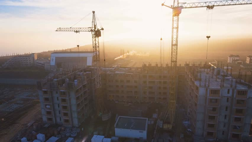 Construction site with a bird's eye on the Sunset. Video shooting with drone. Tower crane, excavator and sand. Flying over the construction site. The construction of the plant in the city. | Shutterstock HD Video #25137635
