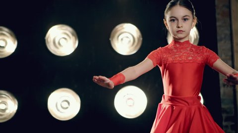 The young girl in red dress dancing cha-cha-cha on stage in bright light
