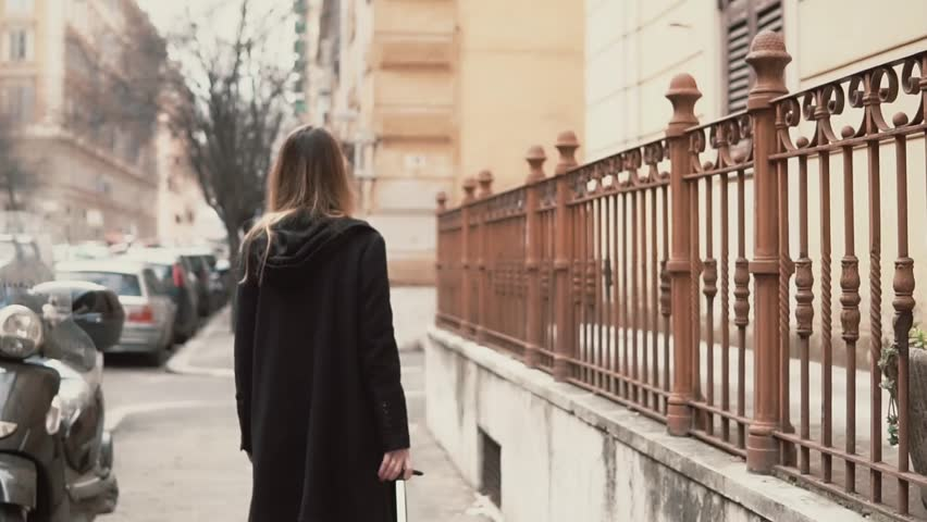 Young woman in black coat walking in the old town part. Back view of the girl exploring the new city. Slow motion. | Shutterstock HD Video #25141166