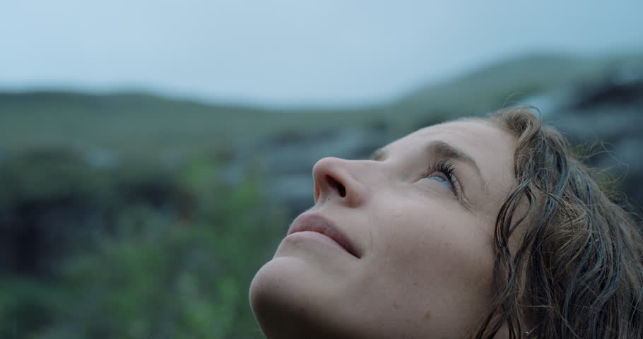Close up portrait of Woman looking up at rain in nature with wet hair Hiker Girl trekking in Scotland Slow Motion | Shutterstock Video #25164725