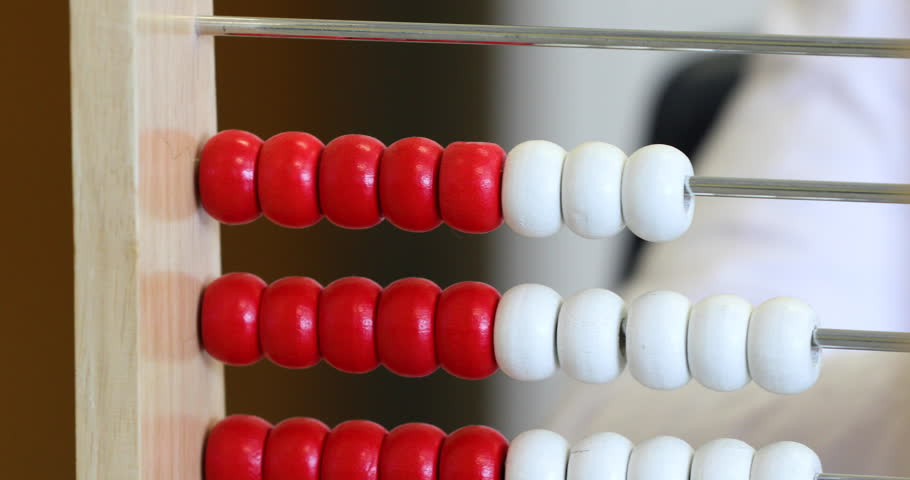 Extreme close up of a child counting using a red and white abacus | Shutterstock HD Video #25171115
