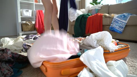 A young woman is haphazardly packing and trying to close the chock-full suitcase. Close up. Time lapse.