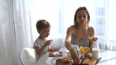 young girl and cute boy eating Breakfast. eat toast and pancakes