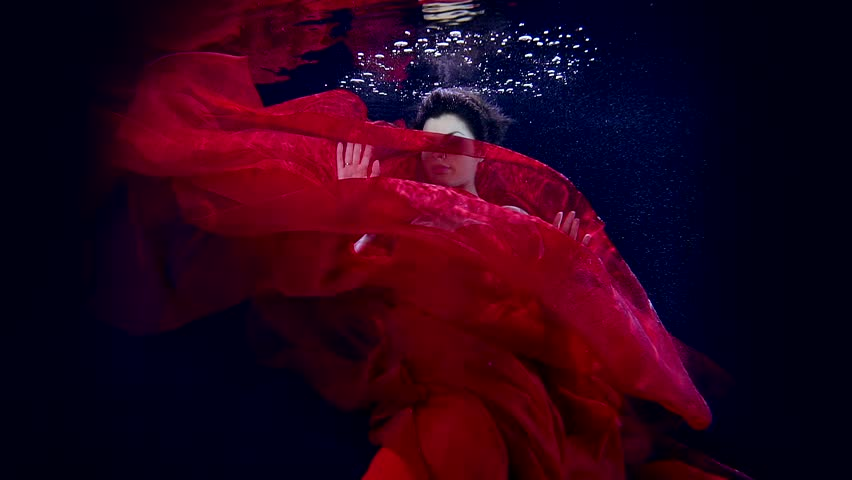 Dance sexy young girl under water in pool Studio contrast lighting. Smooth red cloth of her dress.