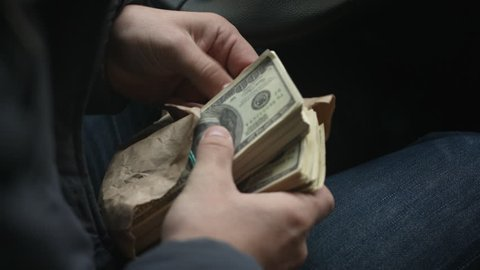 View from over shoulder of man pulls from the package large sum of money sitting behind the wheel of car, close up shots