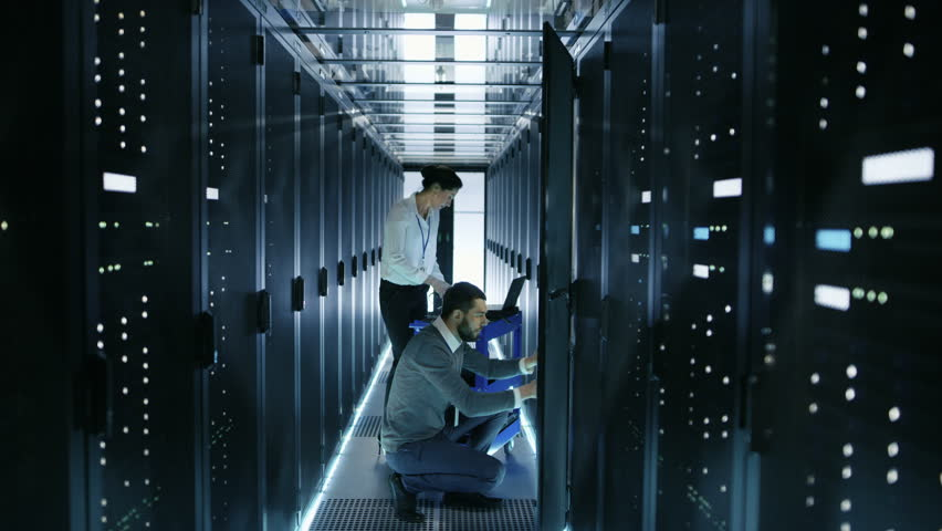 Male IT Engineer Takes out Hard Drives From Rack Server and Gives Them to Female IT Specialist, She Scans Them. They're Working in Big Data Center. Shot on RED EPIC-W 8K Helium Cinema Camera.