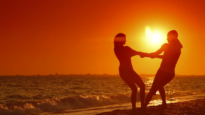 Silhouettes of  young couple spinning on the beach at sunset