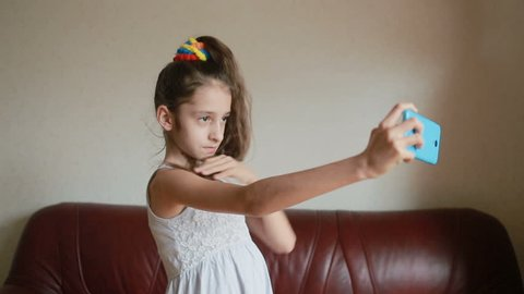 Little girl doing selfie on smartphone at home on couch