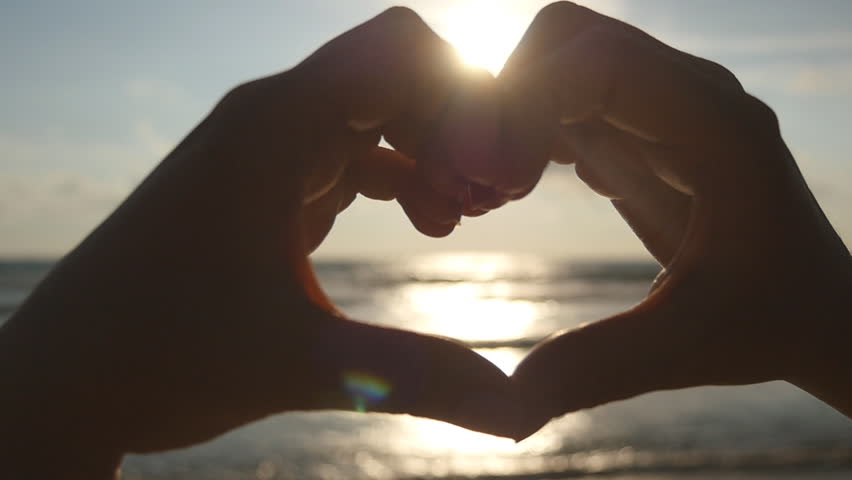 Girl making heart with her hands over sea background with beautiful golden sunset. Silhouette of female arm in heart shape with sunrise inside. Vacation concept. Summer holidays on beach. Slow motion | Shutterstock HD Video #25287365