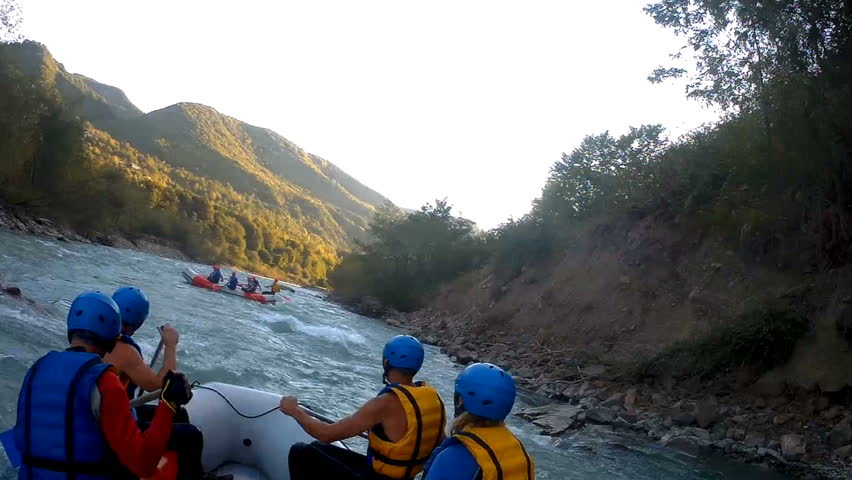 Teams paddling boats along wild mountain river, dangerous white water rafting