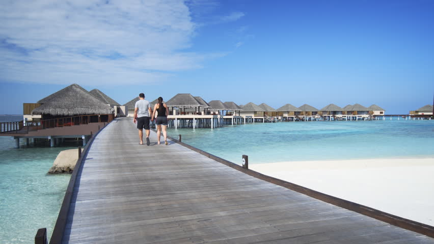 Waves lap gently at the white sand beach at this luxury resort tourist couple holding hands for a romantic stroll along the pier at a luxury resort on publicscrutiny Gallery