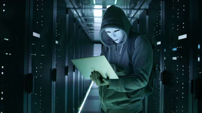 Close-up Shot of a Masked Hacker in a Hoodie Standing in the Middle of Data Center full of Rack Servers and Hacking it with His Notebook. Shot on RED EPIC-W 8K Helium Cinema Camera. | Shutterstock HD Video #25324265