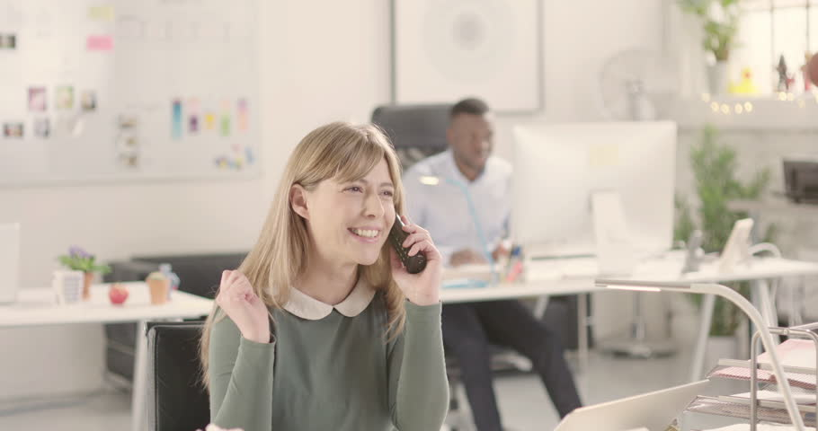 Happy confident woman talking on a phone in a startup office - jib down. Raw version available on request | Shutterstock HD Video #25330355