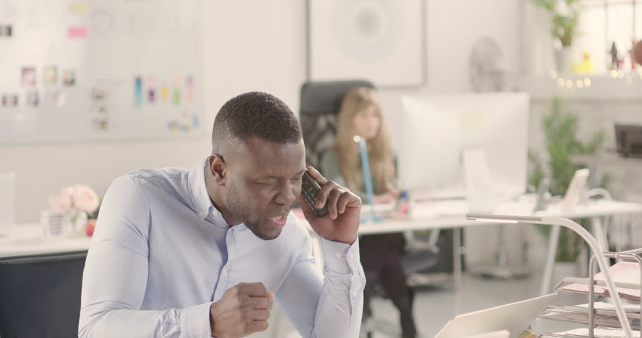 Angry frustrated adult talking on a phone in a startup office - jib down. Raw version available on request | Shutterstock HD Video #25330388
