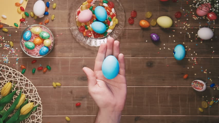 Hand holding easter egg in front of table decorated with easter eggs. Top view | Shutterstock HD Video #25343015