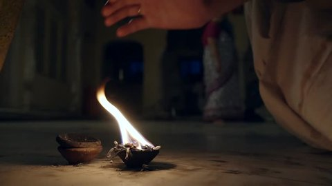 moment of prayer in the temple of Krishna with oily candle and bathed in fire