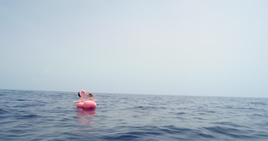Woman lying on inflatable flamingo floating in middle of ocean girl relaxing in summer sunshine enjoying tropical vacation | Shutterstock HD Video #25362035