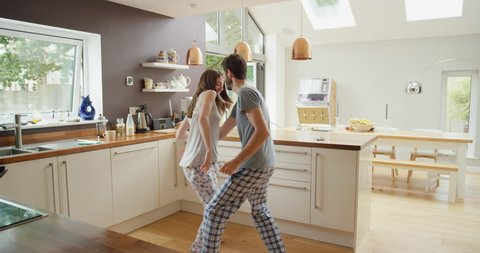 Happy young couple dancing in kitchen wearing pajamas listening to music morning at home