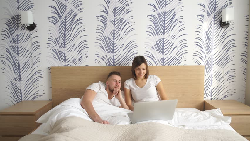Smiling Using A Laptop Lying On Their Bed 4k Stock Footage Clip