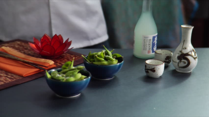 Lock down shot of chef pouring hot sake with bowls of Edamame (soy beans) on the side.