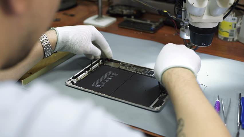 Electronics repair. Master repairs bad gadgets, the tablet  | Shutterstock HD Video #25434935
