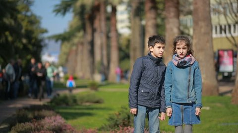 Brother and sister fights and pushes each other in the street against the backdrop of palm trees