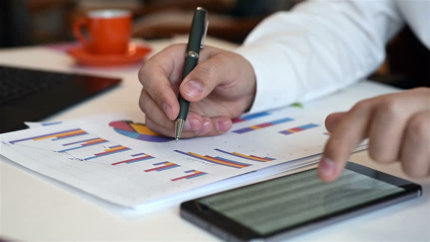 Business Broker Analyzing Stock Charts On Paper. Mobile Phone With Busines Report On Table