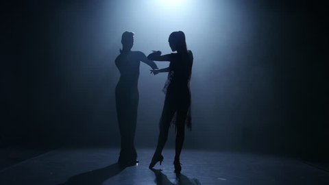 Dance element from the ballroom-sport program, silhouette couple ballroom. Smoke