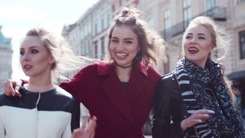 Close up view of gorgeous women wandering in the city center and communicating, smiling, laughing. Stylish outlook. Windy weather. Busy center. True friendship. Embracing each other.