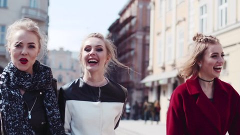 Happy three friends wandering in the old city center, laughing, and joking. The woman in a red coat hugs her friend. Stylish modern women. Having fun with true friends.