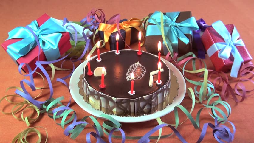 Big Chocolate Cake With Birthday Candles Burning Between Gift Boxes