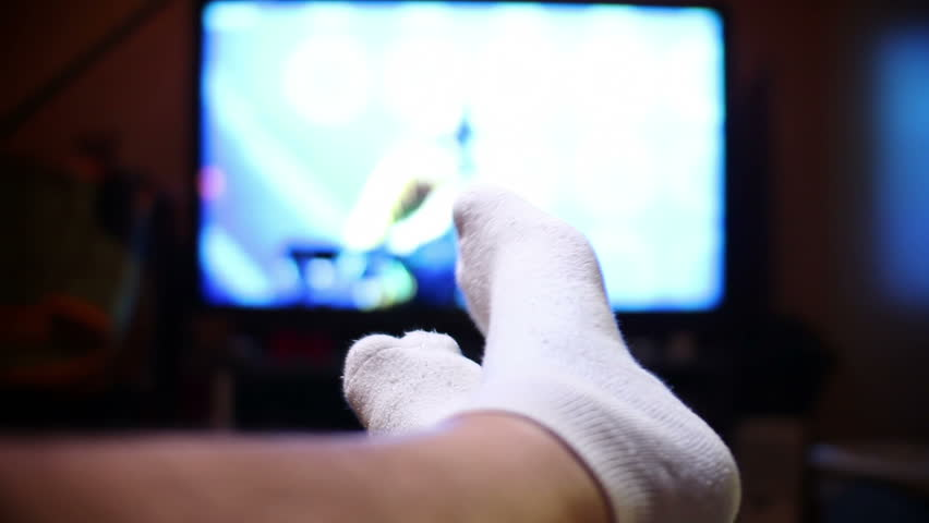 A man watches television, relaxing with his feet up.  Extreme shallow DOF.