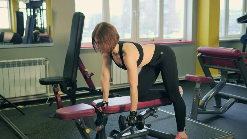 Woman Doing Back Exercises With Dumbbells For Development Of