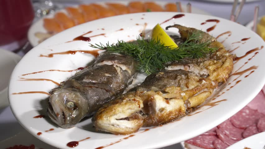 Tasty fried fish decorated on plate
