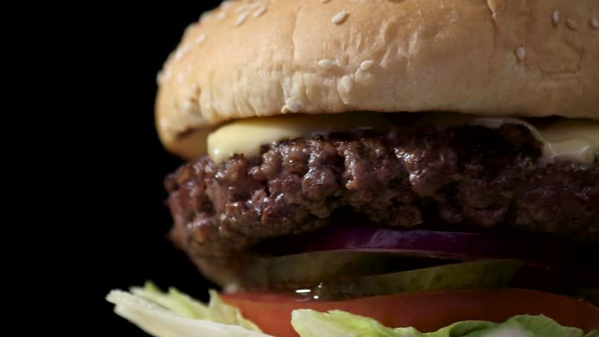 Cheeseburger on black background. Closeup of burger rotating.