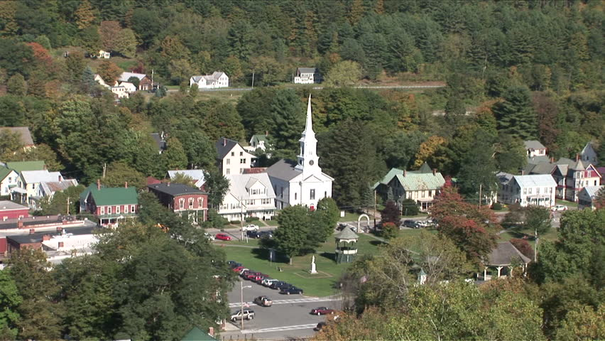 Wide view of a quiet country town in the middle of a forest with a church