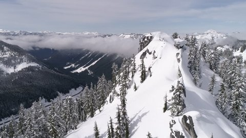 Winter Roadtrip Aerial with Pan from Snowy Cliffs to Reveal Highway 2 in Pacific Northwest