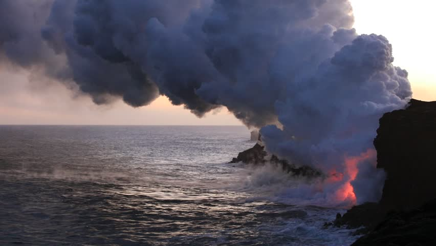 Beautiful dawn landscape of sea Water meeting Lava Fire. Steam cloud lit with red colored light of fire rising from ocean where volcanic lava flowing into a water at the edge of rocky shoreline