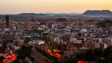 Costa Blanca, Spain. Aerial view of Alicante, Spain in the evening. It is a popular summer resort of Costa Blanca. Time-lapse, illumination at sunset. Mountains at the background