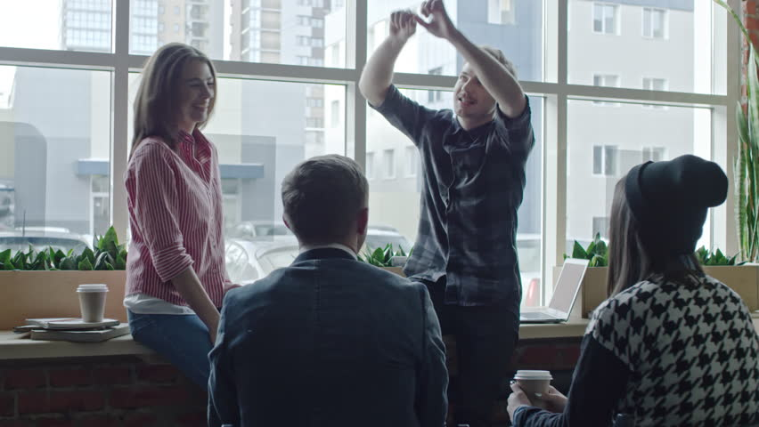 Young Business Team Having Active Discussion In The Office Hipster Guy Sitting On Window Sill